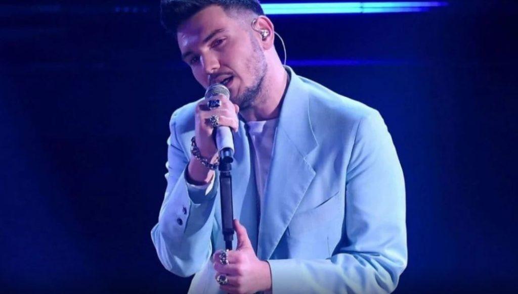 sanremo 2021 quarta serata - gaudiano vincitore delle nuove proposte. indossa una giacca azzurra e tiene il microfono nella mano destra