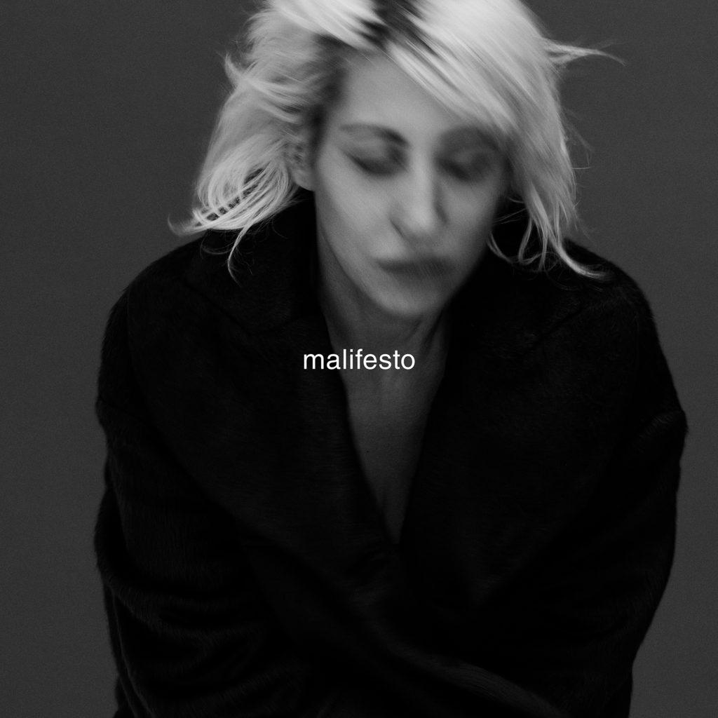 malifesto, la foto copertina dell'album ha il nome stampato al centro, è in bianco e nero con Malika mossa, indossa una maglia nera