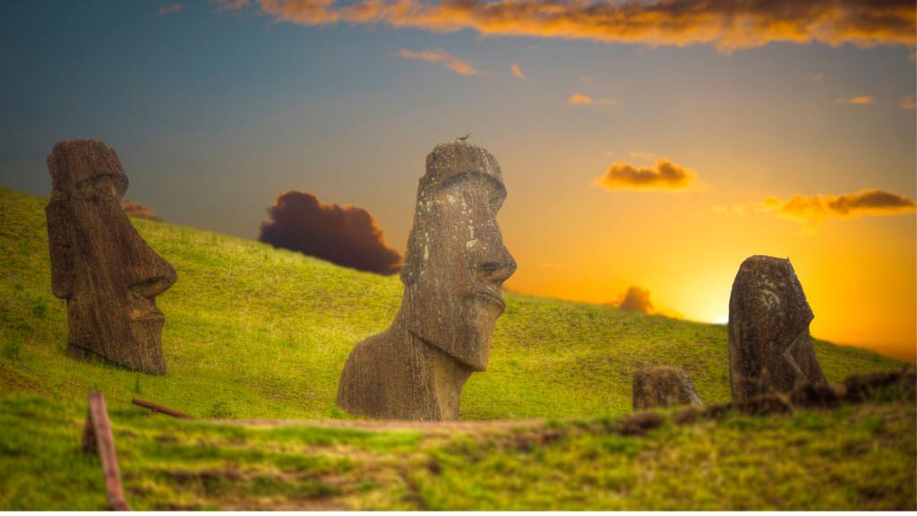 Le famose statue di teste di pietra piantate sul versante di una collina verde. Il cielo è un tramnto arancione