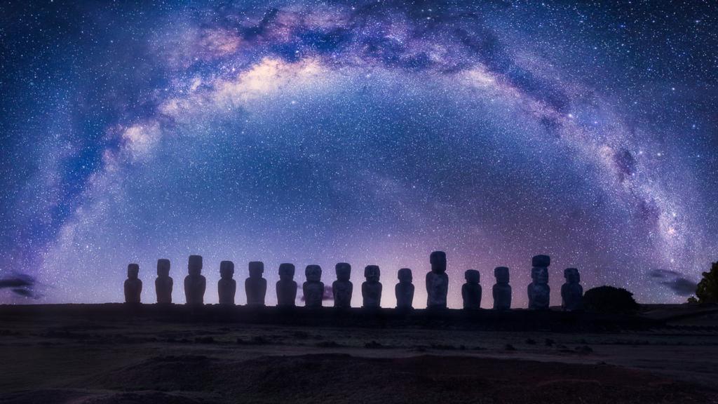 Isola di Pasqua - le statue di pietra fotografate di schiena, di notte. Il cielo è blu e le nuvole fanno un arco nel cielo