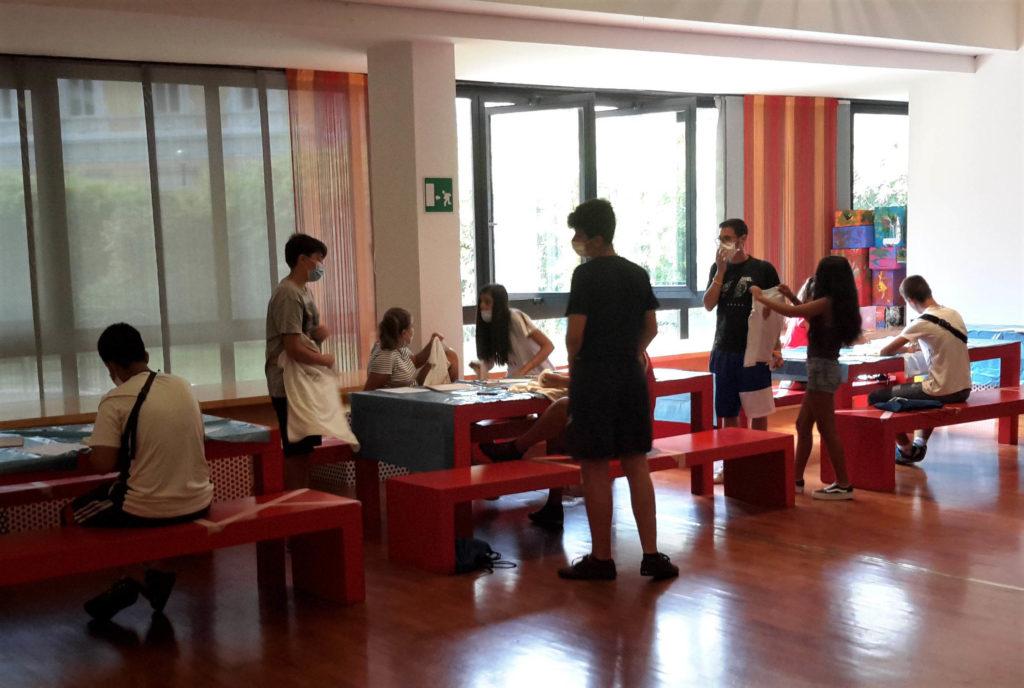dei bambini in una aula con dei banchi rossi stanno svolgendo attività creative