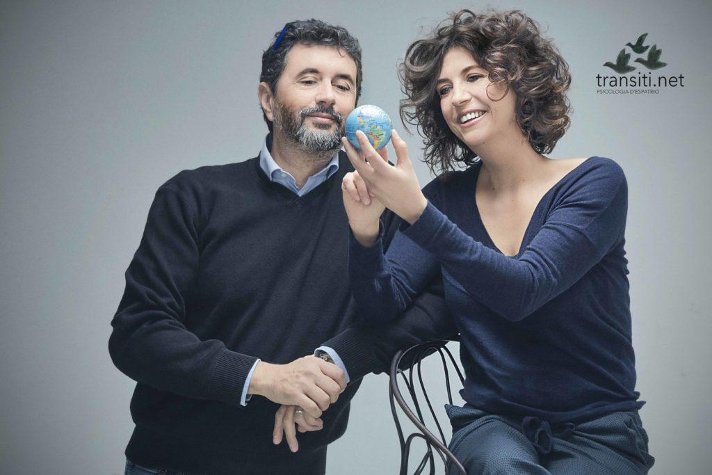 TRansiti -  Anna-Pisterzi-e-Mauro-Sclavo seduti vicini vestiti entrambi con un maglione scuro, guardano sorridendo un piccolo mondo tenuto in mano da Anna