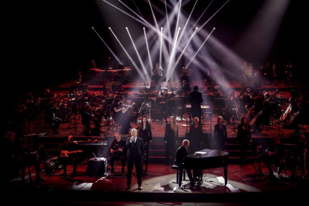 Claudio Baglioni durante le prove dello spettacolo con tanti ballerini con le luci viola