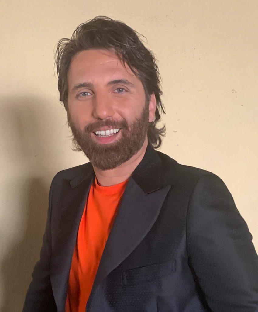 stai con me - nella foto giancarlo sorride in posa con t shirt rossa, giacca scura. Ha capelli lunghi sulle spalle e barba curata