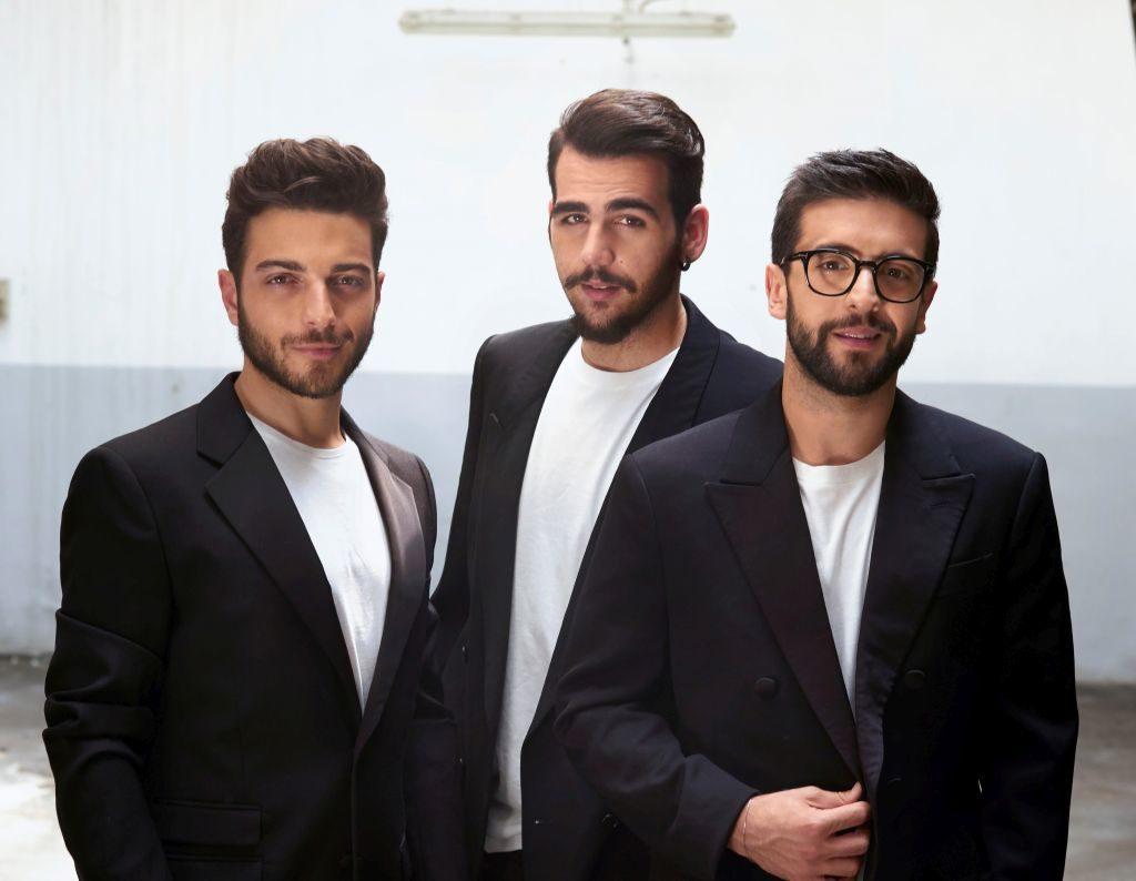 Il volo tre ragazzi giovani, tutti e tre con barba ben curata corta, capelli corti, sono vestiti con t shirt bianca e giacca smoking nera