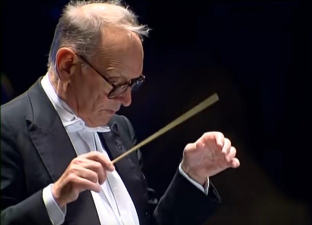 Ennio Morricone, anziano, di profilo, con occhiali da vista con montatura scura, indossa camicia bianca e giacca nera, sta dirigendo un'orchestra con la bacchetta nella mano destra