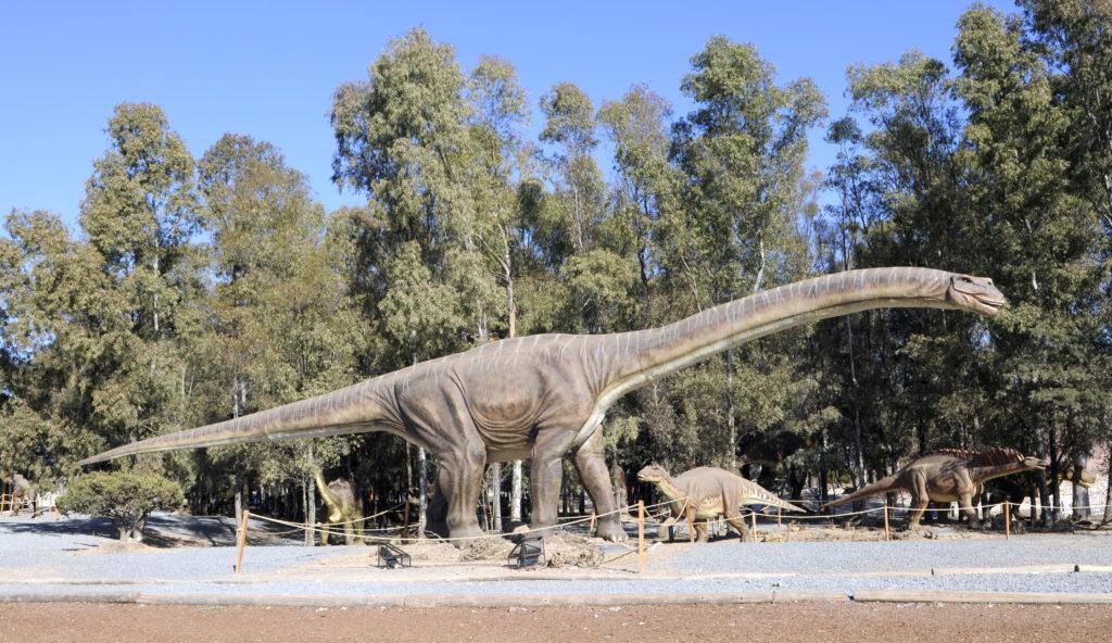 un branchiosauro con un collo molto lungo e lunga coda nel verde di un parco