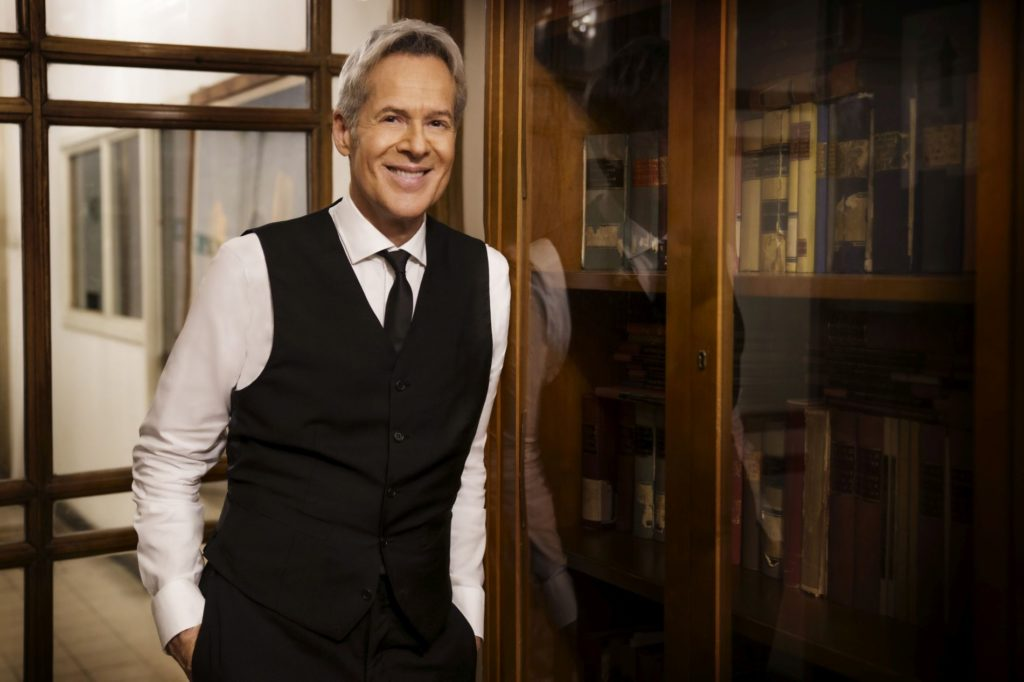 Claudio Baglioni con camicia bianca e cravatta nera, camicia bianca, sorride, appoggiato ad un armadio con le vetrine