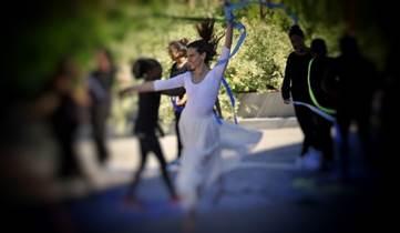 GAM - una ragazza vestita di bianco danza con braccia in alto e la gamba destra piegata, intorno alei altri ballerini danzano in un parco