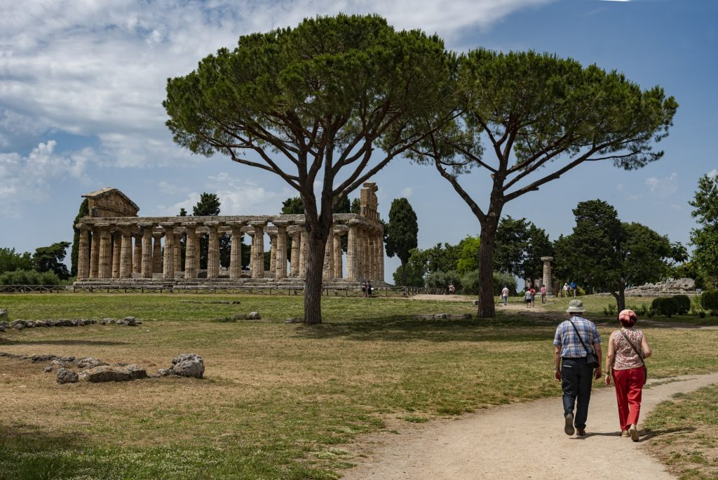 Paestum il tempio visto da lontano , con un prato, le rovine del tempio fatto di colonne. Sulla destra, una coppia di turisti passeggia sulla strada sterrata