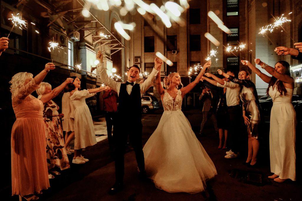 Due sposi fanno la passerella tra gli invitati. La sposa ha un bellissimo abito bianco lungo e llargo al fondo, lo sposo, ha vestito scuro, entrambi hanno le braccia alzate.