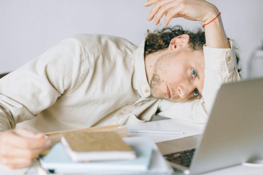 Pandemic fatigue - un uomo seduto davanti a un pc appoggia la testa sull'interno del braccio piegato, con un'aria molto triste. sulla scrivania ci sono dei libri
