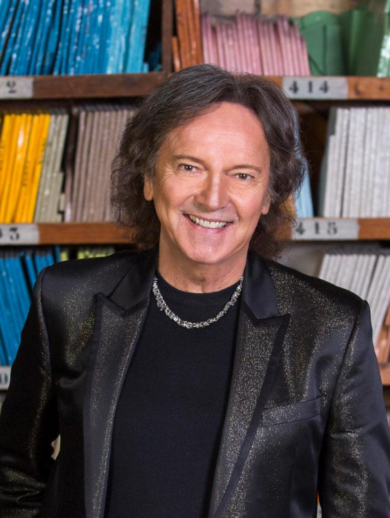 red canzian, sorridente, veste t shirt nera, giacca di pelle nera, un girocollo in argento. Ha lunghi capelli mossi sulle spalle, dietro di lui una libreria piena di libri