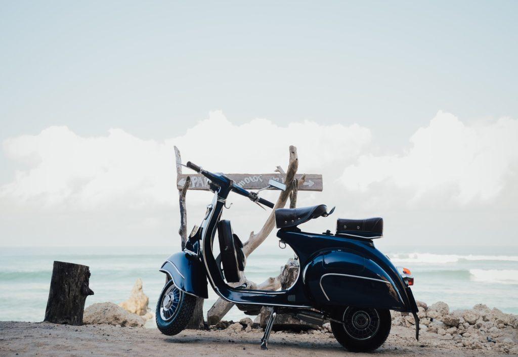 anni 60 .una vespa blu parcheggiata davanti alla spiaggia, sullo sfondo il mare