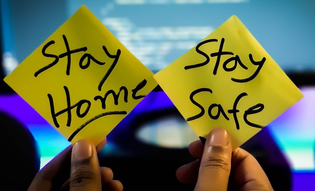 """Pandemic Fatigue - in primo piano due post it con la scritta """"stay home"""" e """"stay safe"""" tenuti da due dita e sullo sfondo un o schermo di pc"""