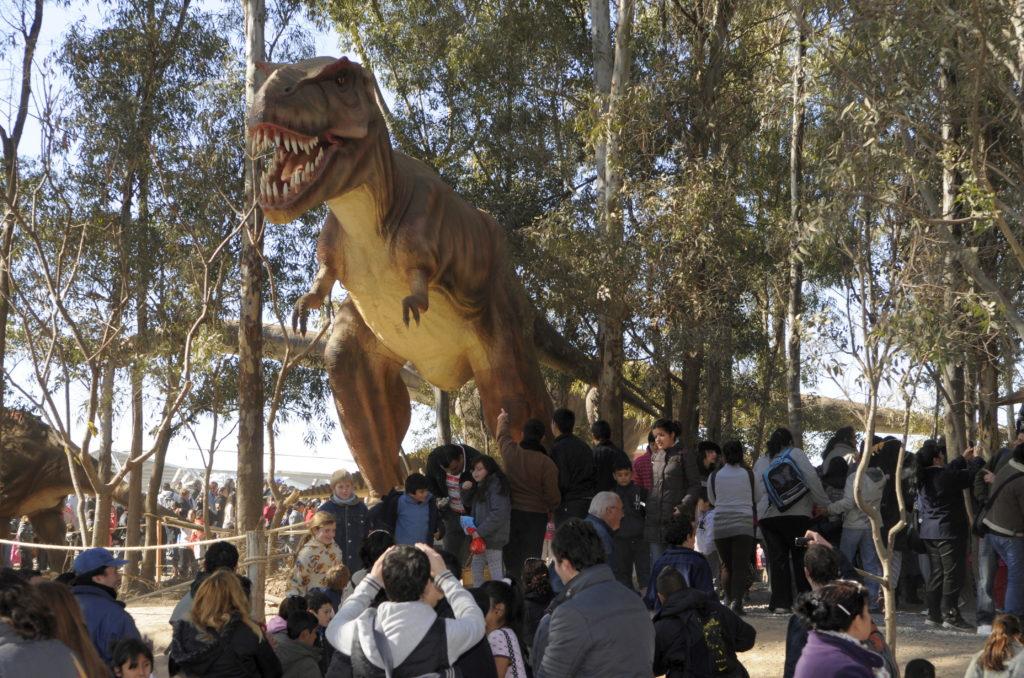 t-rex a grandezza naturale con grandi denti aguzzi e un'espressione feroce. Sotto di lui diversi visitatori del parco, con bambini e adulti