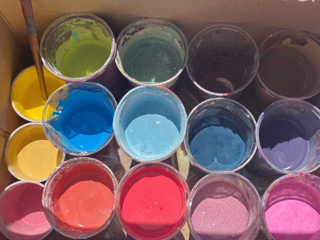 Una scatola piena di vasetti con della pittura colorata verde, azzurra, rossa, viola, arancione blu e gialla