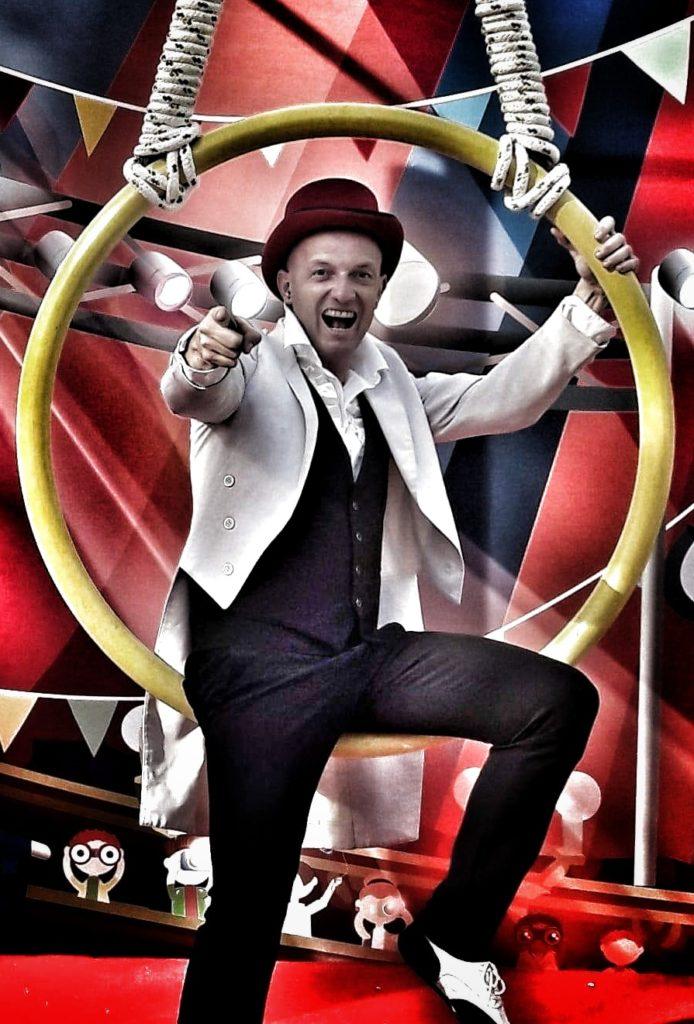 Mister David & Family Dem nella foto è seduto su un cerchio da circo. Indossa un cilindro, giaccca bianca, pantaloni e gillet nero e ha il braccio destro teso in avanyti e con l'indice indica l obiettivo, dietro di lui la scenografia rossa di un circo