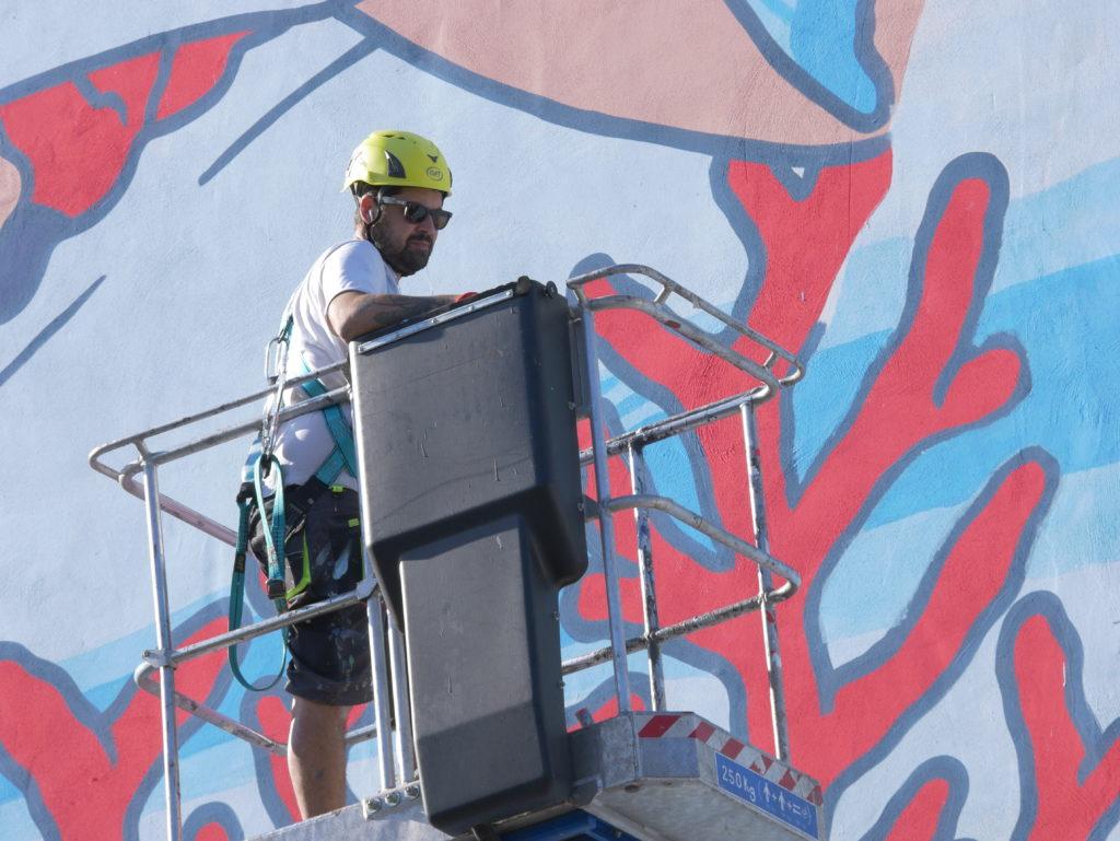 Lucamaleonte nella gabbia di una gru sollevatrice s, con caschetto di sicurezza, sta disegnando il murales