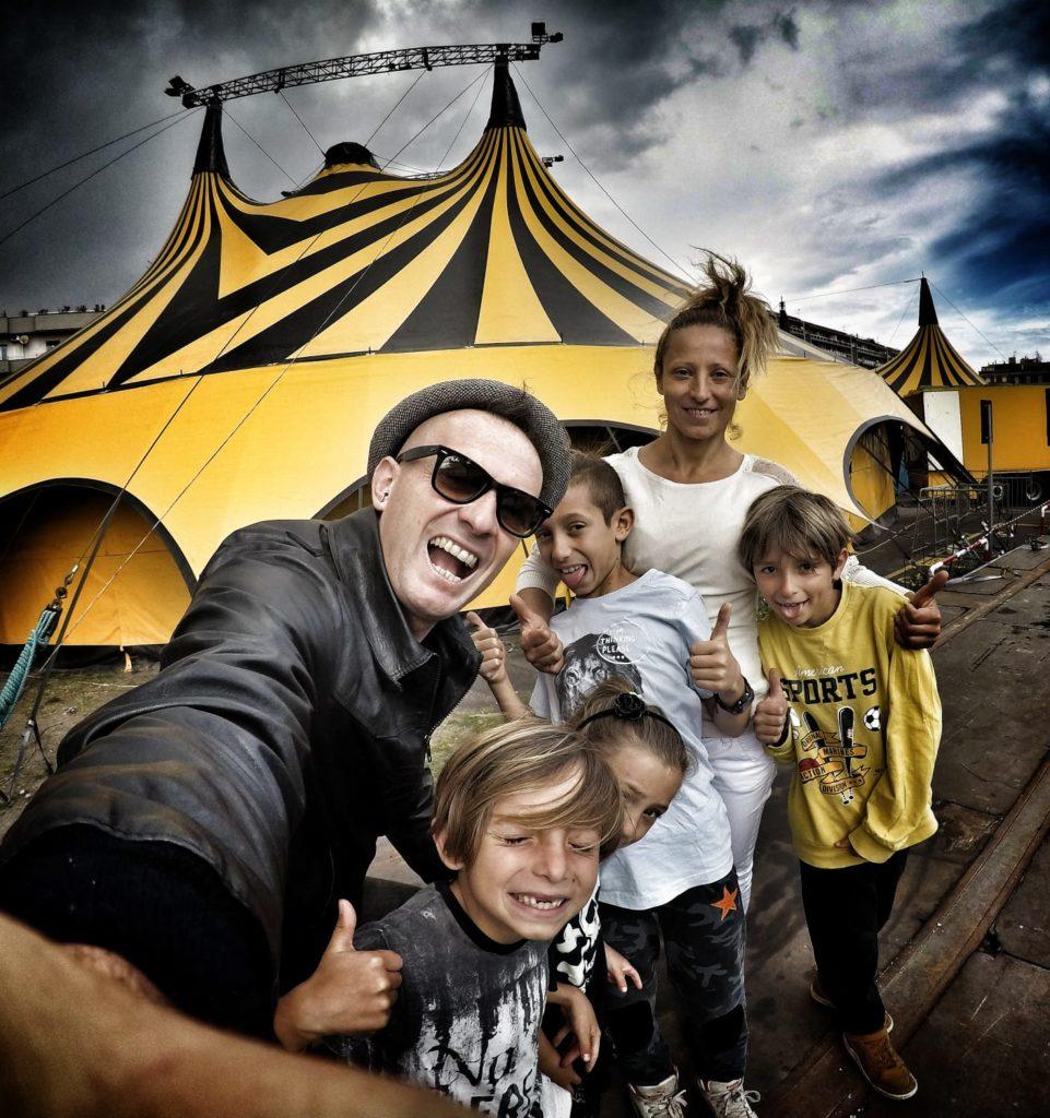 Mister David & The Family Dem: con mister David ci sono la moglie e i bambini, dietro di loro il tendone da circo giallo e nero