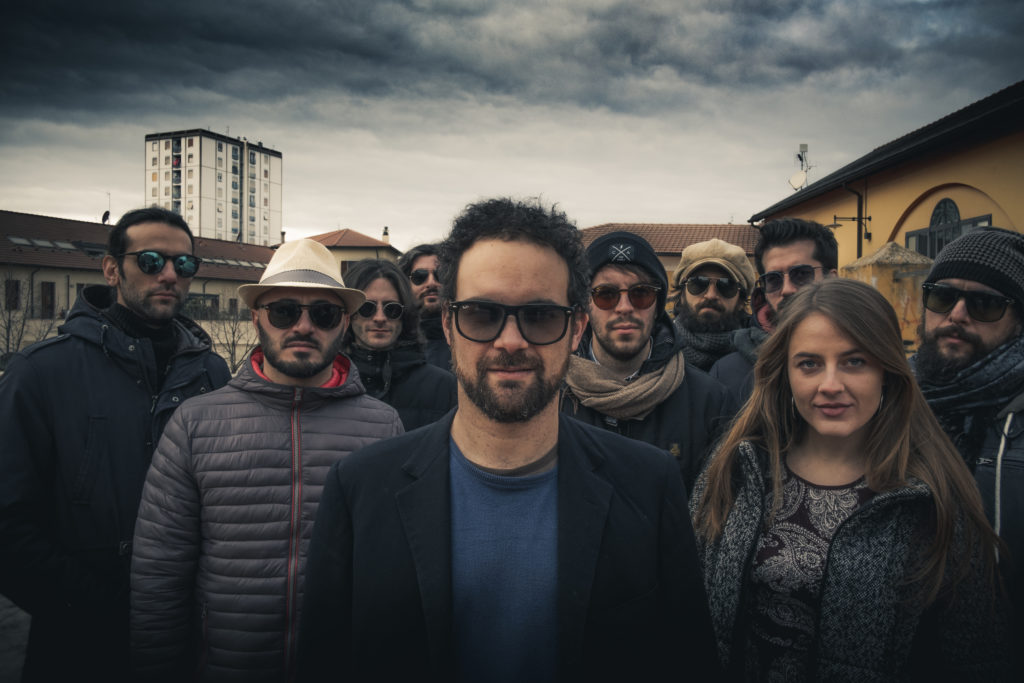 l'orchestra Magna in un afoto di gruppo all'aperto con dietro un cielo nuvoloso