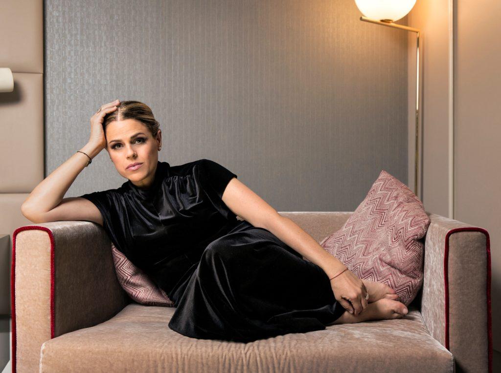 Visioninmusicaosca sdraiata su un divano, indossa maglia e pantalone nero, ha la testa appoggiata sul braccio