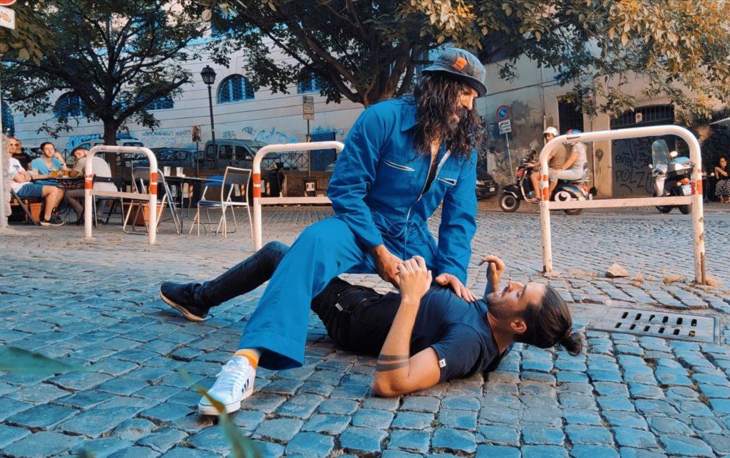 Tomas Milian - nella foto Rocky atterra con un amossa da wrestling un uomo con capelli raccolti, vestito con maglia blu e pantaloni neri. Rocky indossa tuta blu da meccanico e cappello, con barba e capelli neri