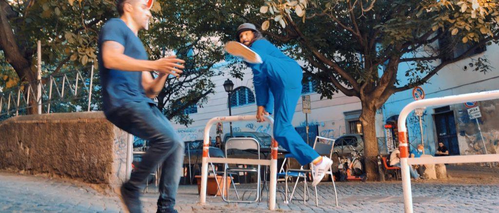 Rocky indossa tuta blu da meccanico e cappello, con barba e capelli neri fa un salto con gamba tesa appoggiandosi allo schienale di una sedia