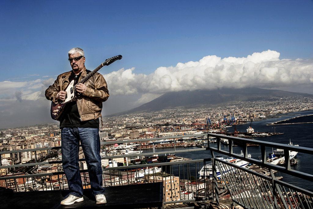 Una veduta panoramica di Napoli e Pino Daniele sulla destra, concapelli bianchi, vestito con jeans e giubbotto beige, mentre suona la chitarra