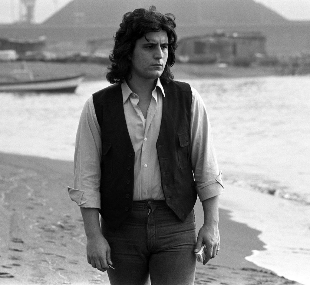 Pino Daniele in riva al mare, passeggia assorto, indossa pantaloni scuri, gillè e camica. foto in bianco e nero