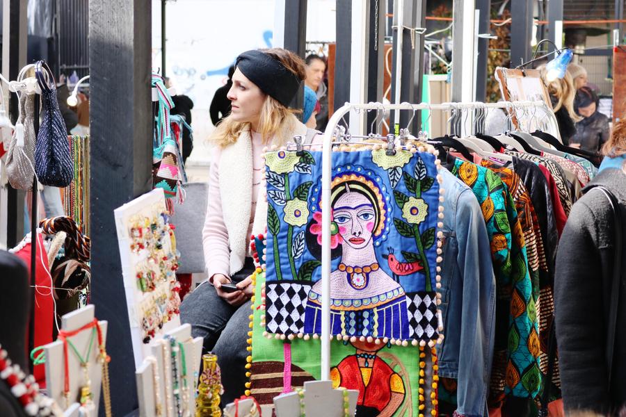 Oktober Fest una ragazza di profilo, dietro un porta abiti con degli abiti appesi in un mercato