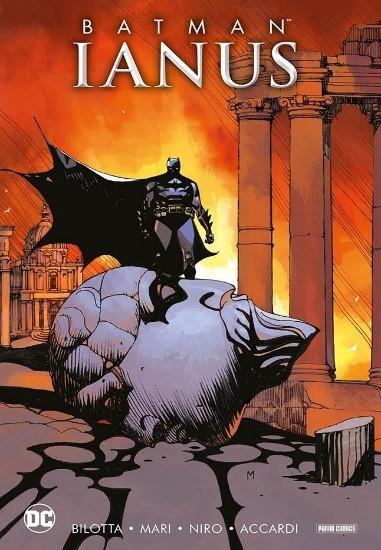 la copertina del fumetto storia Ianus con Batman con il mantello nero svolazzante, in piedi su un masso che cadendo ha crepato tutto l asfalto e dietro di lui due colonne con uno sfondo rosso e arancione giallo