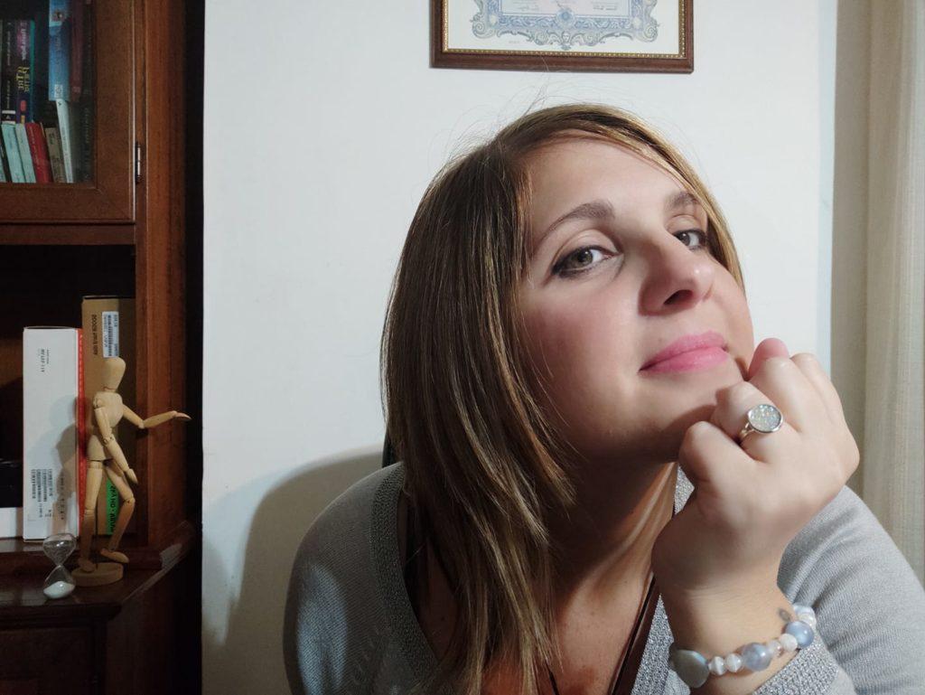 Mimma Leone seduta in asa, appoggia il mento sul pugno. Ha lunghi capelli biondi e indossa un maglione azzurro. Dietro di lei si intravede un quadro e lo stipite di una porta di un mobile libreria