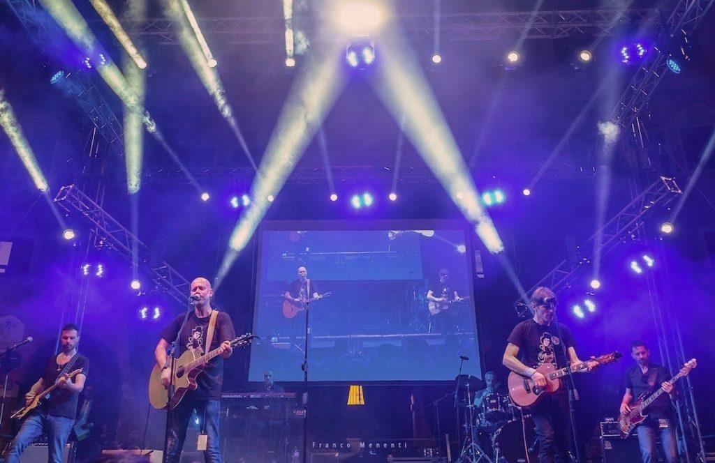 Mei 2021 - nella foto sul palco del mei la Rino Gaetano Band con luci biaanche su sfondo azzurro