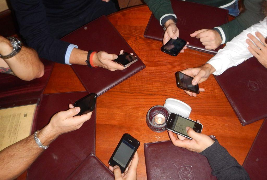 phubbing - nella foto si vede un tavolo dall'alto con tante cartelline marroni, tante mani che tengono un cellulare