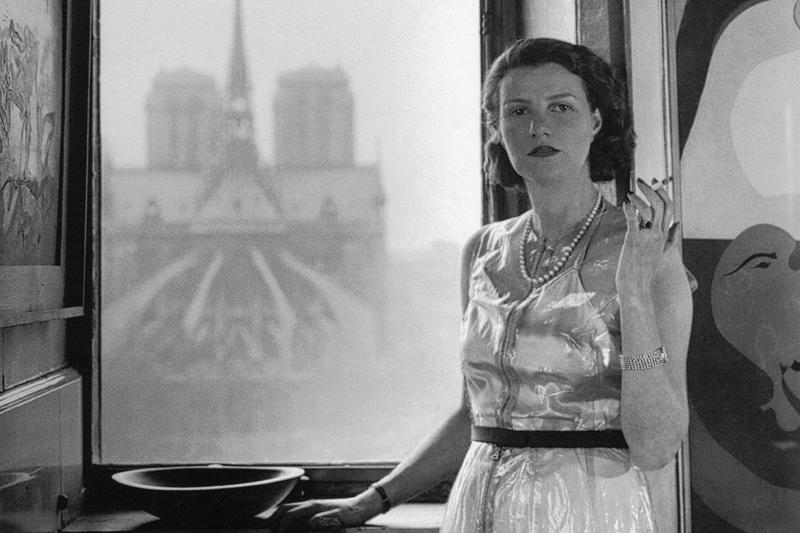 Peggy Guggenheim a Parigi fotografata da Rogi André, 1940. Foto in bianco e nero lei inpiedi davanti alla. Finestra con sigaretta.
