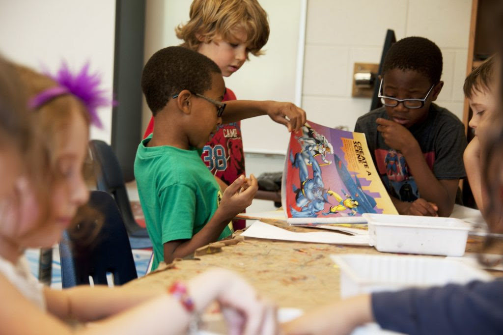 nella foto ci sono dei bambini che stanno producendo attività di laboratorio ad un tavolo, uno ha in mano un disegno colorato, un altro bimbo di colore ha in mano delle matite e l'altro disegna